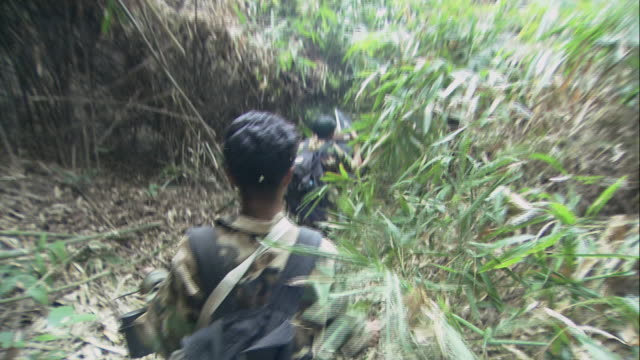 pov column of soldiers walking through stands of brush and clearing a path with machetes / thailand - natural column stock videos and b-roll footage