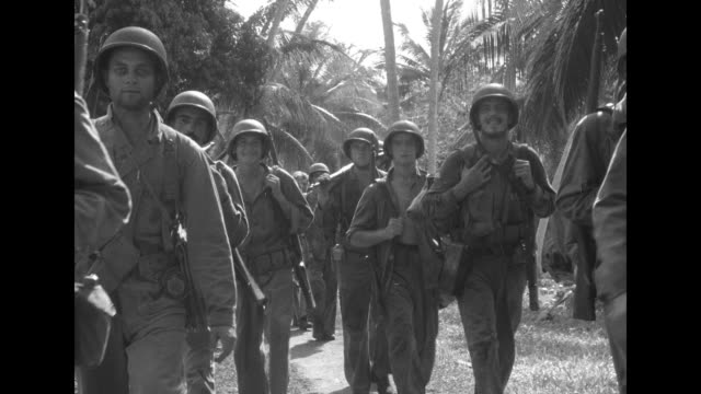 VS column of US Marines marching along path through jungle / VS Marines sitting resting / two shots of Marines putting up barbed wire barrier on...