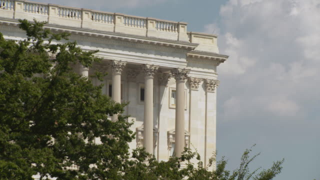 stockvideo's en b-roll-footage met a columned wing of the united states capitol building as seen over a tree, washington, d.c., usa. - senaat verenigde staten