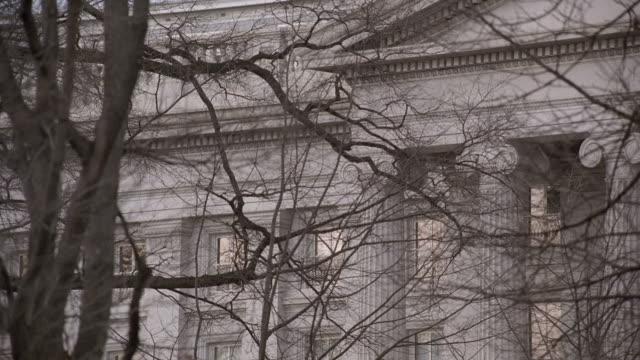 vídeos y material grabado en eventos de stock de pan columns of the commerce department building through bare tree branches / washington, d.c., united states - entabladura