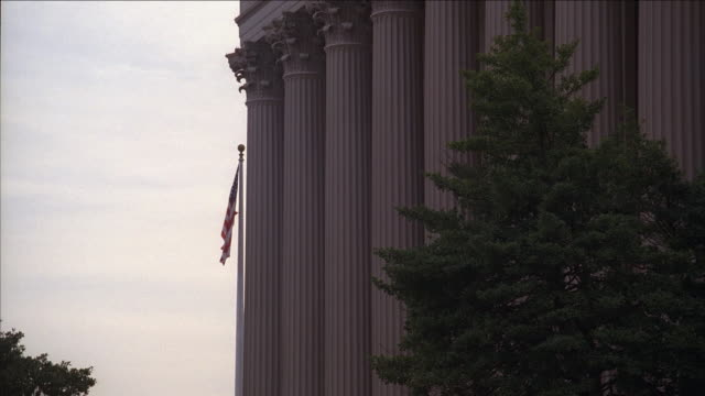 la columns of the national archives building with american flag / washington, d.c., united states - national archives washington dc stock videos and b-roll footage
