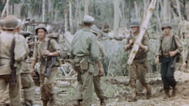 ws columns of us marines walking along dirt road in opposite directions and jungle and lvt loaded with soldiers on guam during wwii pacific campaign... - グアム点の映像素材/bロール
