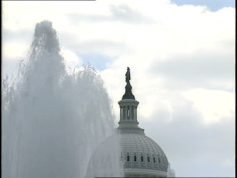 stockvideo's en b-roll-footage met columns of water fall from senate fountain partially obstructing the us capitol dome with statue of freedom in bg - neoklassiek