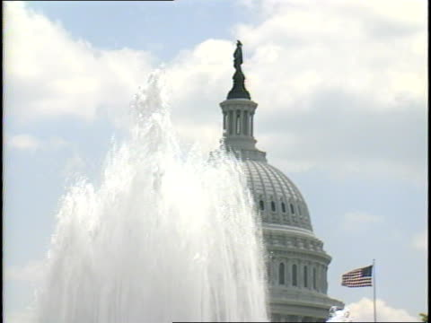 stockvideo's en b-roll-footage met columns of water fall from the senate fountain partial view of the capitol dome statue of freedom and us flag in bg - neoklassiek