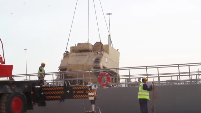Combat armed vehicles being loaded aboard the US Army's SP/4 James A Loux or LSV6 at the Port of Shuaiba Kuwait The equipment was transported to the...