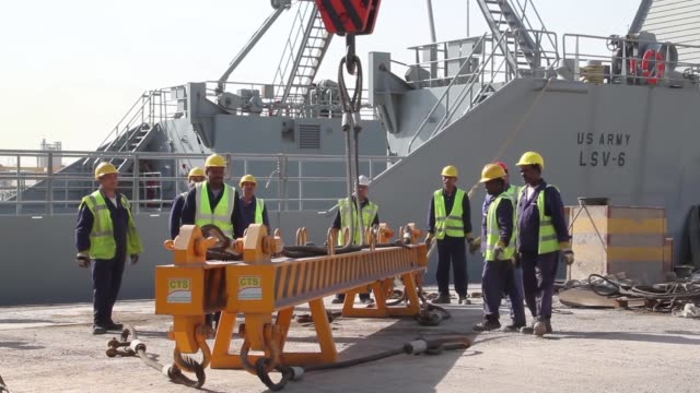combat armed vehicles being loaded aboard the us army's sp/4 james a loux or lsv6 at the port of shuaiba kuwait the equipment was transported to the... - 湾岸諸国点の映像素材/bロール