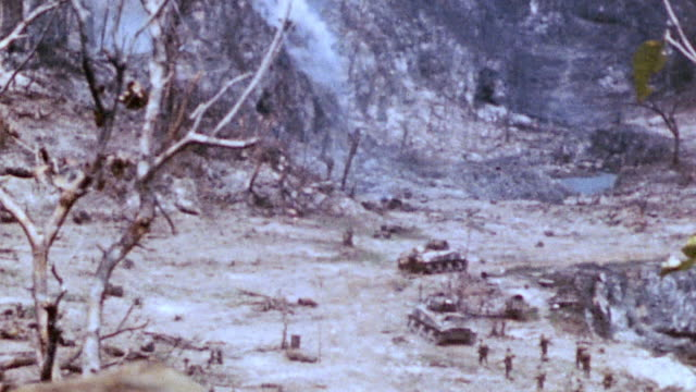 combat infantry and m4 sherman tanks fighting across rocky and wooded terrain smoke drifting and tanks firing at cave mouth / iwo jima japan - schlacht um iwojima stock-videos und b-roll-filmmaterial