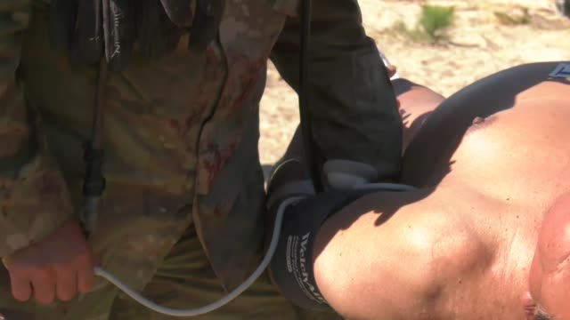 A combat medic team with the Idaho Army National Guard practice administering immediate medical aid to acting casualties for response training...