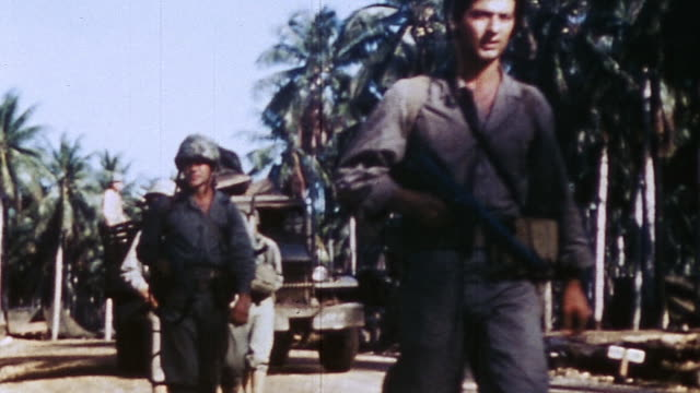 LA Combat ready US Marines advancing on dirt road with loaded truck slowly passing by during WWII / Peleliu Palau