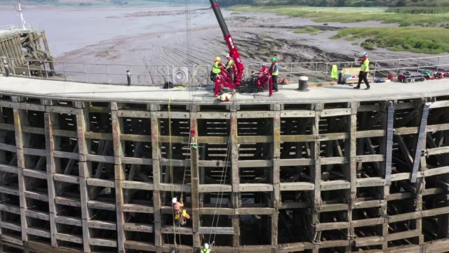 a combination of rockclimbing skills and a spider crane is being used to repair a decadesold timber pier the work at sharpness dock in... - rock climbing stock videos & royalty-free footage