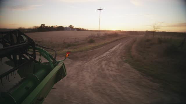 Combine drives along a rural farm road.
