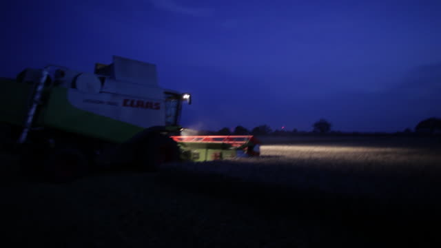 combine harvester working in field at night - combine harvester stock videos & royalty-free footage