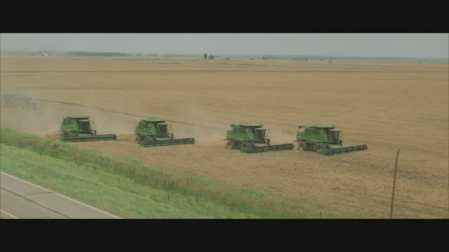 cs, ts, combines in field and traffic on rural road - convoy stock videos and b-roll footage