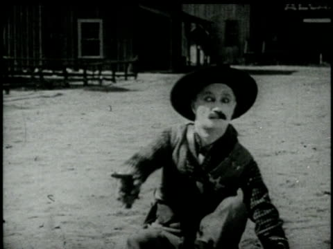 1920 b/w montage ms comedian ben turpin as sheriff, unsuccessfully trying to shoot pistol before pistol goes off as he shoves it in his trousers/ usa - abfeuern stock-videos und b-roll-filmmaterial