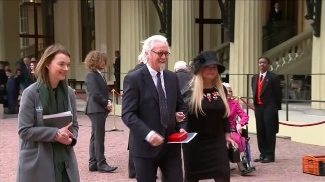 vidéos et rushes de comedian billy connolly receives knighthood ext sir billy connolly and wife along outside palace connolly posing with award - billy connolly