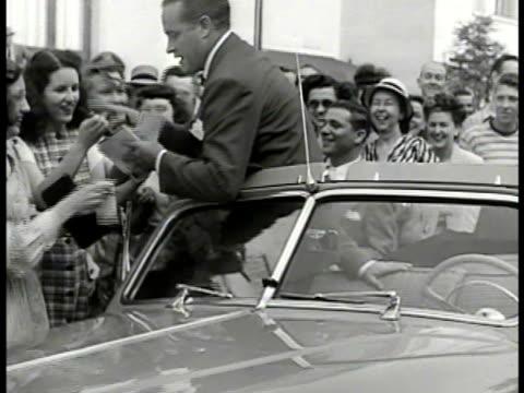 comedian bob hope walking to convertible car w/ young women autograph seekers following extending books pens. crowd watching bg. bob hope taking... - bob hope komiker stock-videos und b-roll-filmmaterial