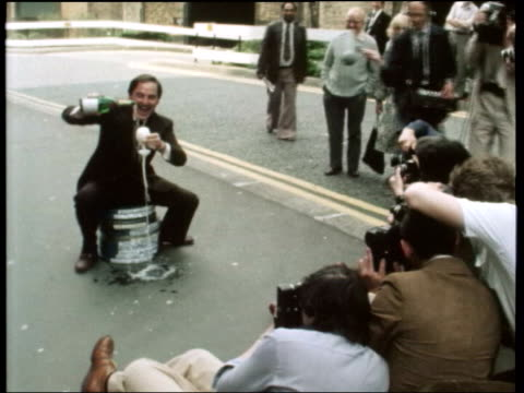 comedian bob monkhouse dies; lib ext monkhouse sitting on film cans pouring champagne into glass for photocall - bob monkhouse stock videos & royalty-free footage