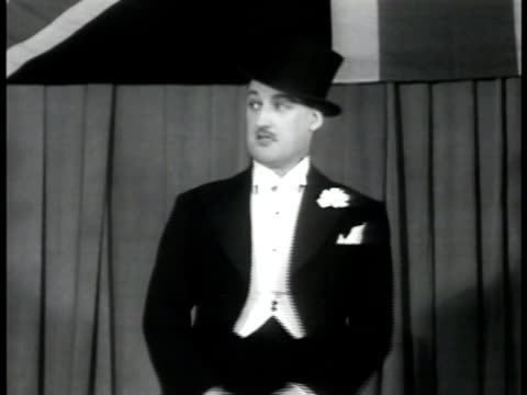 vídeos y material grabado en eventos de stock de comedian in top hat & tails performing on stage, telling joke about news traveling fast. australian soldiers in audience applauding. wwii - sombrero de copa