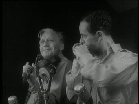 Comedian Jack Benny plays violin with harmonica virtuoso Larry Adler during a USO show