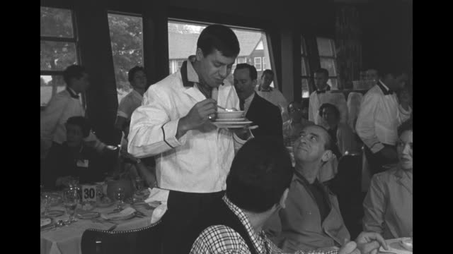 comedian jerry lewis, dressed as a waiter, takes customer's soup bowl off table in restaurant, eats from it / lewis carries tray laden with dishes,... - comedian stock videos & royalty-free footage
