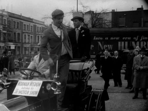 comedian norman wisdom arrives at the earls court motor show and immediately starts to joke around with the waiting crowd. 1952. - earls court stock videos & royalty-free footage