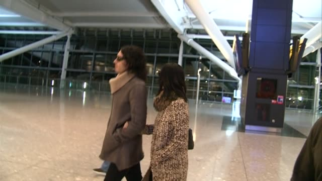 Comedian Russell Brand and singer Katy Perry walk arm in arm at Heathrow as they board flight Perry avoids camera although Brand dressed in heavy...