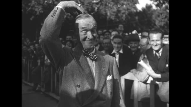 comedian stan laurel mugs for the camera scratches his head as he arrives at the french festival of the stars at the tuileries garden crowd watches... - stan laurel stock videos & royalty-free footage
