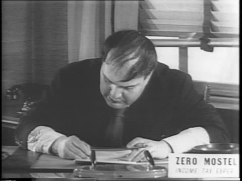 vídeos de stock e filmes b-roll de comedian zero mostel playing a tax expert / montage of mostel lifting his head from a desk covered in books at a desk with a woman sitting upon his... - formulário documento
