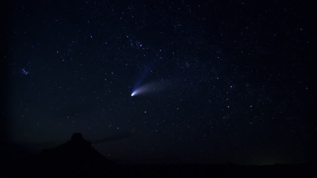 a comet descends on the horizon as night falls onto the desert. - 彗星点の映像素材/bロール