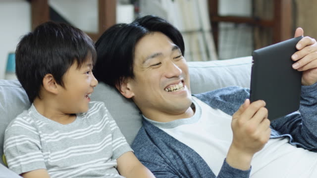 comfortable father and son playing tablet computer game - japanese ethnicity stock videos & royalty-free footage