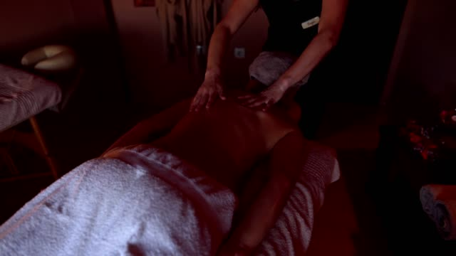 comfortable female customer on a massage table getting massaged - massage table stock videos & royalty-free footage