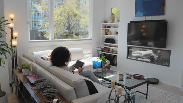 comfortable woman relaxes on her couch with her tablet in a smart home - internet of things stock videos & royalty-free footage