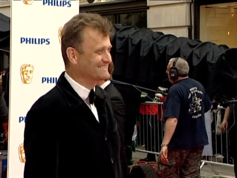 Comic actor Hugh Dennis smiles for the photographers at the BAFTA awards in London