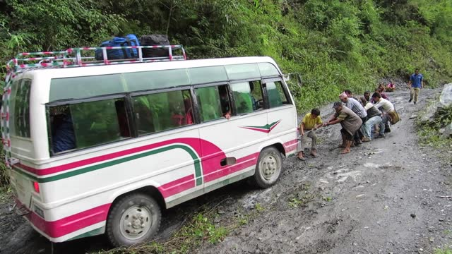 comic real time video of men trying to free a bogged bus on the beni jomsom sadak dirt road which runs along the kali gandaki river in a densely forested area on the road from beni to jomsom, nepal. - humour stock videos & royalty-free footage