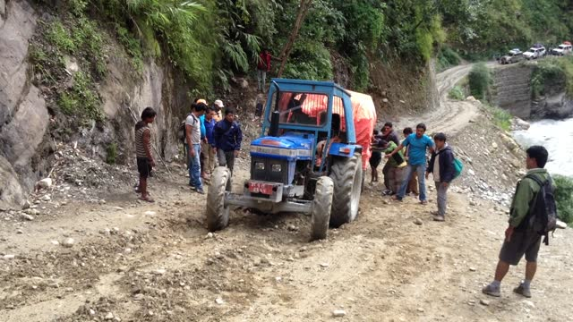 comic real time video of men trying to free a bogged tractor on the beni jomsom sadak dirt road which runs along the kali gandaki river in a steep ravine with a cliff on one side and a steep drop off on the other on the road from beni to jomsom, nepal. - mistake stock videos & royalty-free footage