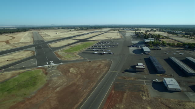 coming in for landing at redding municipal airport in shasta county, california, aerial view. - hangar stock-videos und b-roll-filmmaterial