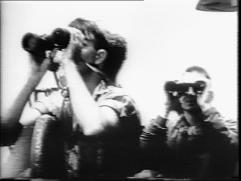 commander george levick street looking through binoculars / crew members looking through binoculars / cameraman filming wearing helmet / men... - 映像撮影点の映像素材/bロール