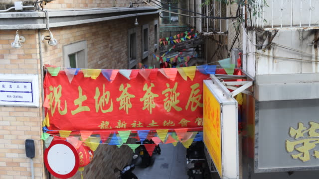 vidéos et rushes de commemorative chinese banner and colourful banderols hanging at a narrow courtyard over parking scooters. - banderole signalisation