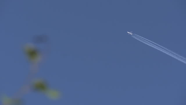Commercial aircraft crossing the blue sky and leaving a smoke trail