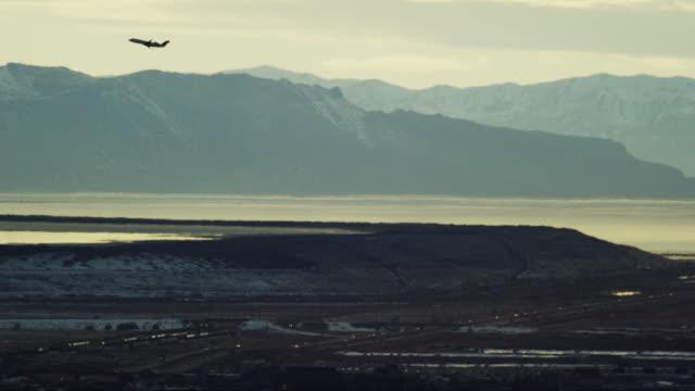 stockvideo's en b-roll-footage met een commerciële lijnvliegtuigjet in silhouet vliegt over het grote zoutmeer in utah en snowcapped mountains in de winter bij zonsondergang op een partly cloudy day - air vehicle