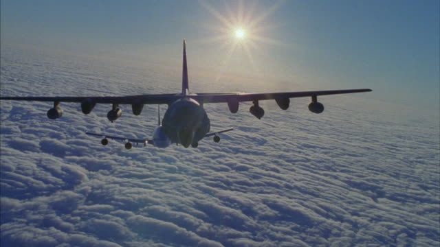 A Commercial airplane flying above a thick layer of clouds.