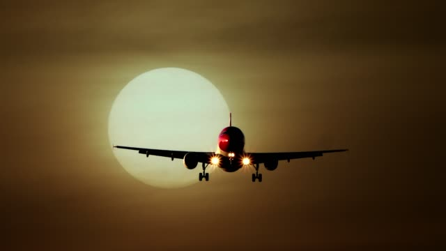 commercial airplane flying and landing at airport with sunset background - コックピット点の映像素材/bロール