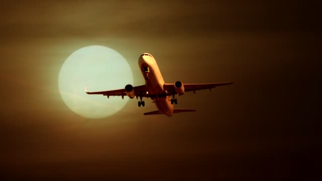 Commercial airplane flying and landing at airport with sunset background