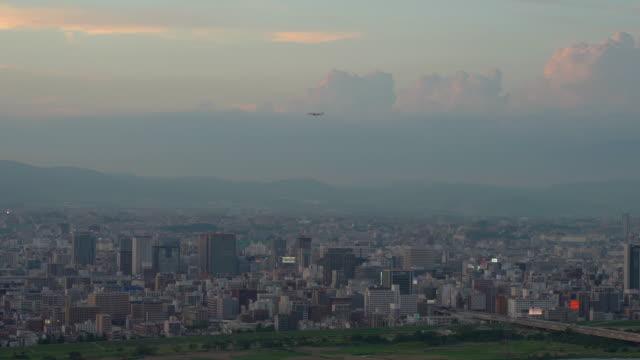commercial airplane over osaka city during sunset - präfektur osaka stock-videos und b-roll-filmmaterial