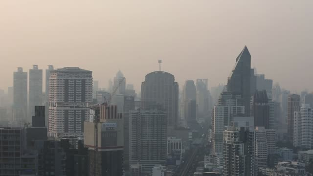 commercial and residential buildings stand shrouded in smog in bangkok, thailand, on thursday, feb. 15 pan across the skyline, photographer: brent... - smog stock videos & royalty-free footage