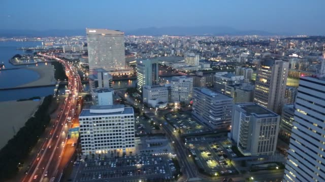 stockvideo's en b-roll-footage met commercial and residential buildings stand silhouetted at sunset in fukuoka japan on friday march 3 traffic flow along a highway at sunset in fukuoka... - stadsdeel