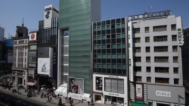 commercial buildings stand in the ginza district of tokyo japan on monday march 20 pedestrians walk past the yamano music co flagship store right in... - music stand stock videos & royalty-free footage