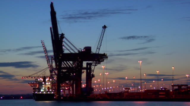 ws pan commercial dock at dusk, hampshire, united kingdom - southampton hampshire stock-videos und b-roll-filmmaterial