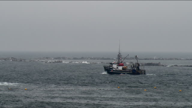 commercial fishing boat chugging past stone jetty in gloomy weather and rough seas - wide shot - fischereiindustrie stock-videos und b-roll-filmmaterial