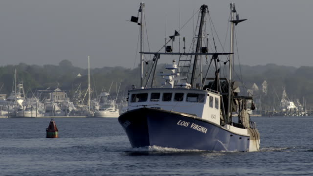 Commercial fishing boat heading out to sea from a small New England fishing village - front view as boat comes towards camera - 1